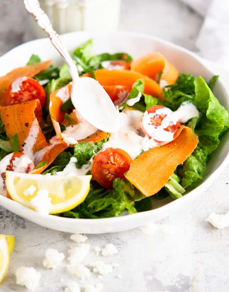 A salad with a creamy feta yogurt dressing drizzled over the top