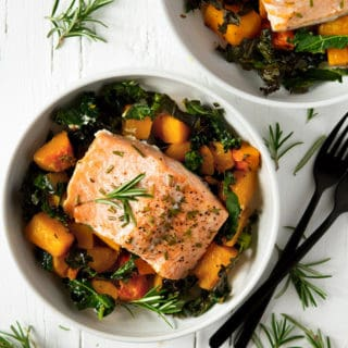 An overhead shot of easy salmon butternut squash and kale in a white bowl topped with rosemary