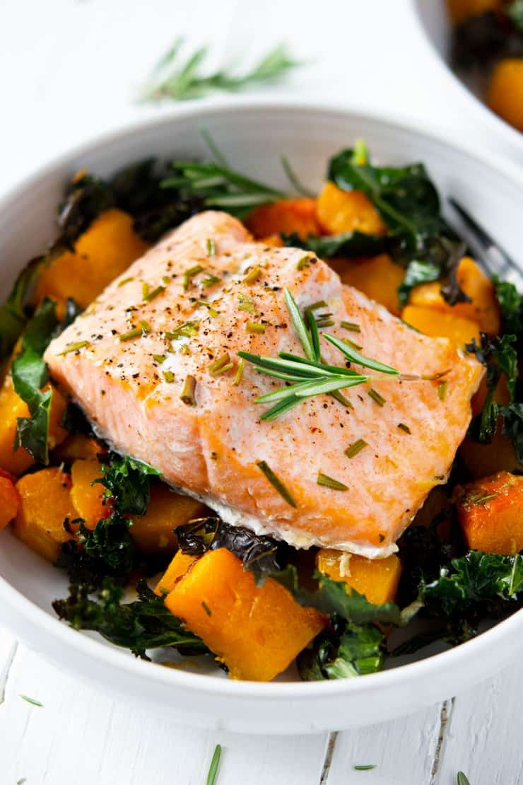 A close up of easy salmon and roasted butternut squash and kale in a white bowl