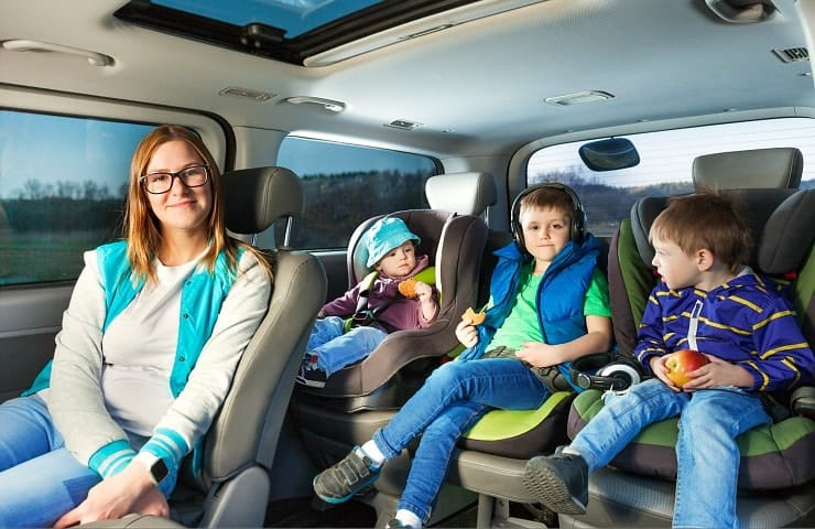 Mom and three kids in car seats for road trip