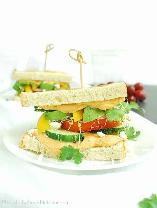 Super healthy vegetable sandwich smeared with red pepper hummus, piled high with fresh veggies, and sprinkled with feta and cilantro | Back To The Book Nutrition