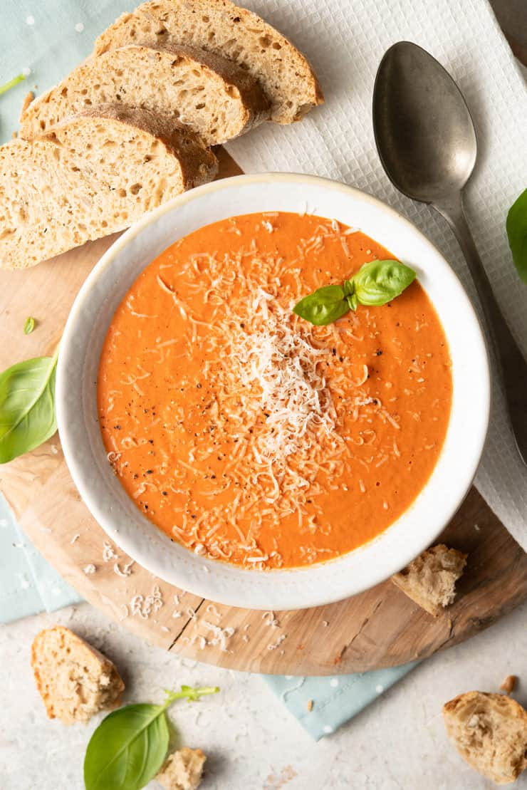 An overhead shot of roasted red pepper soup in a bowl with slices of bread and basil
