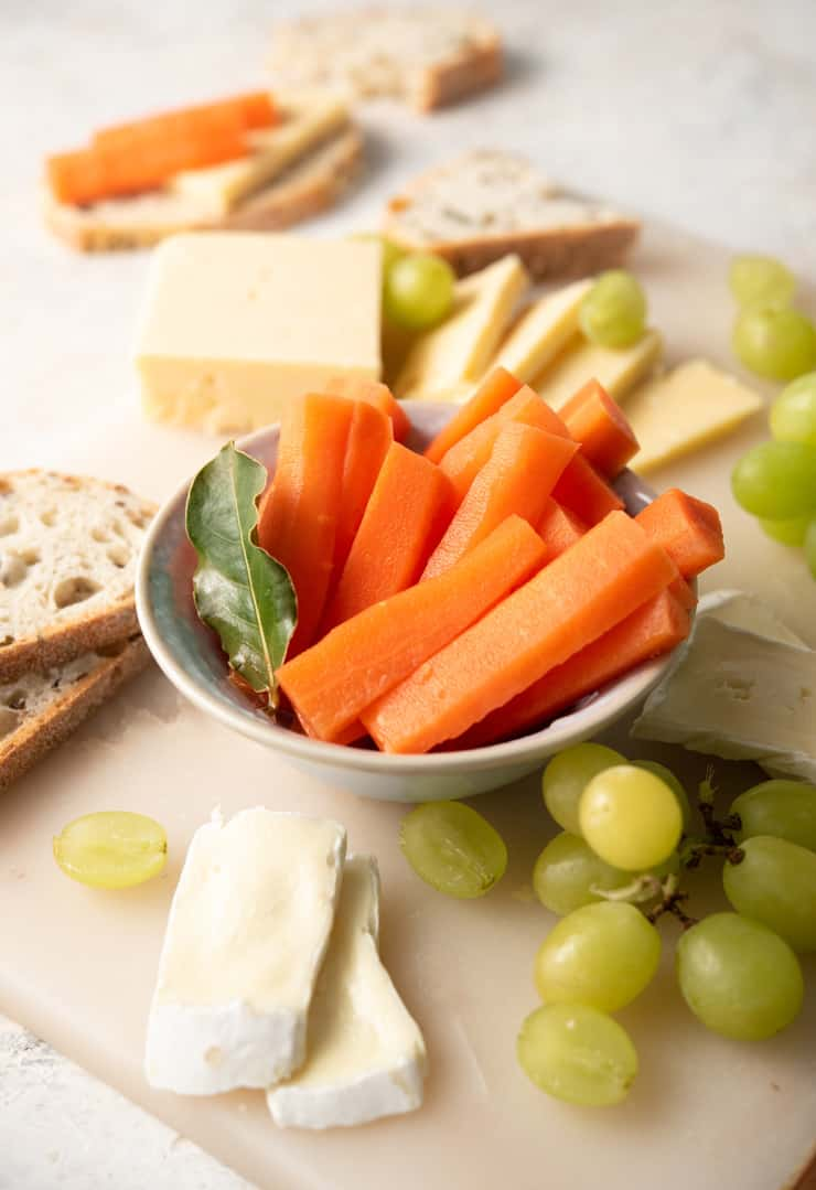 A close up of fermented carrots in a serving dish with cheese and grapes