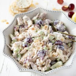 Rotisserie chicken salad in a white dish with grapes and crackers