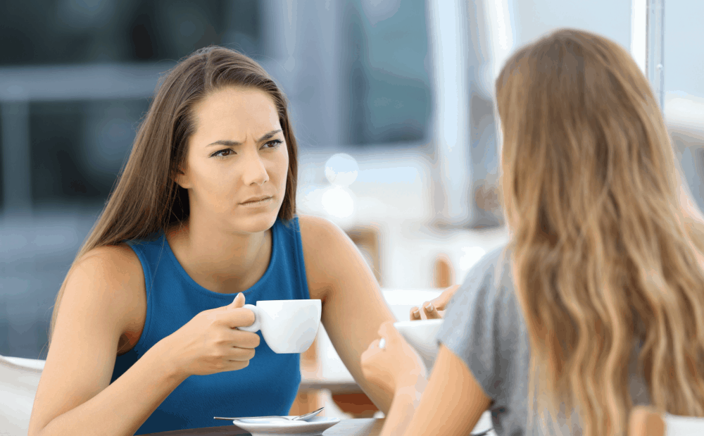 two young woman in serious conversation at coffee shop
