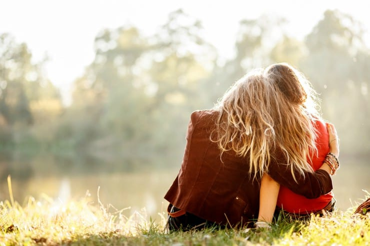 two girls sitting in field hugging