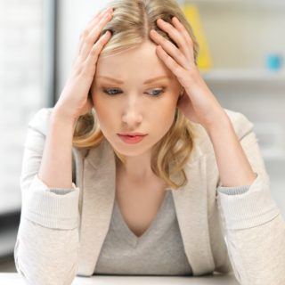 blonde woman feeling stressed at her work desk